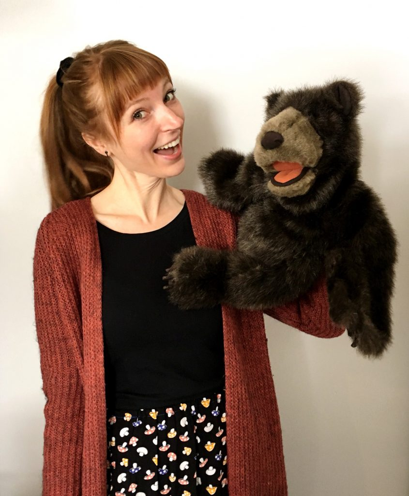 woman smiling and holding a bear puppet