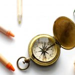 antique compass with pencil crayon and crayons