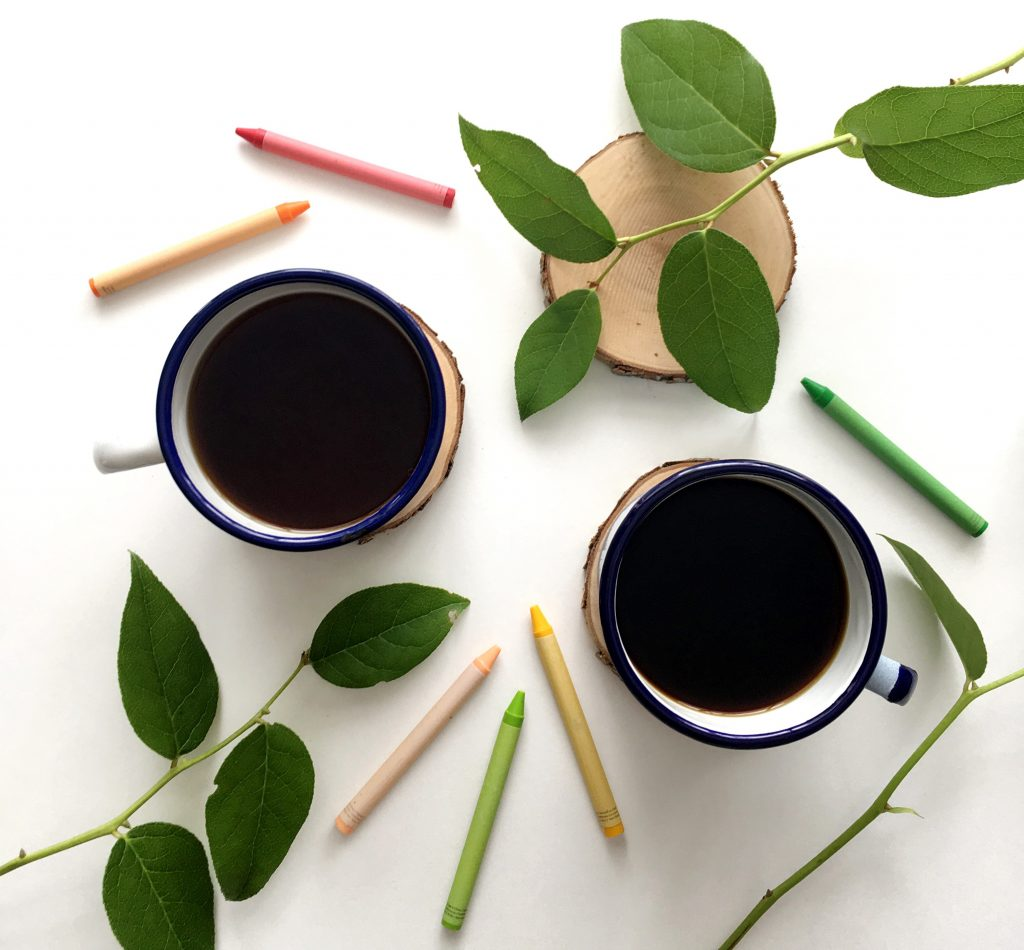 two tin coffee cups, art supplies, leaves on white background