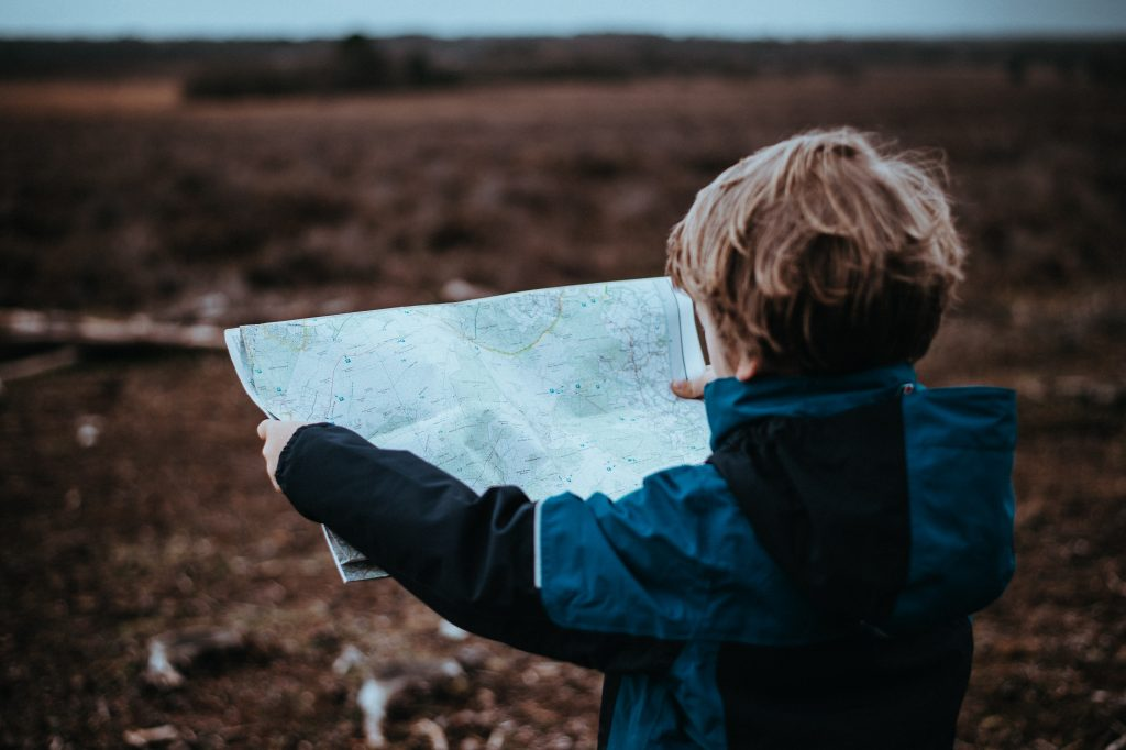 boy holding a map and looking out at a field