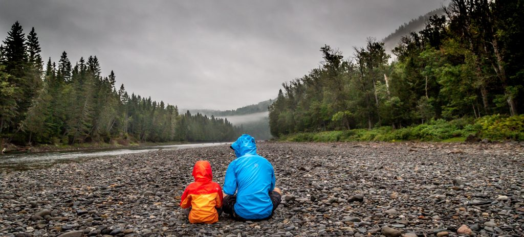 adult and child wearing rain jackets sitting outside in nature
