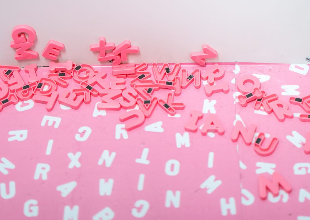 pink alphabet magnets in a pile