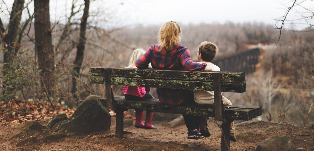 woman sitting on bench in forest with two children