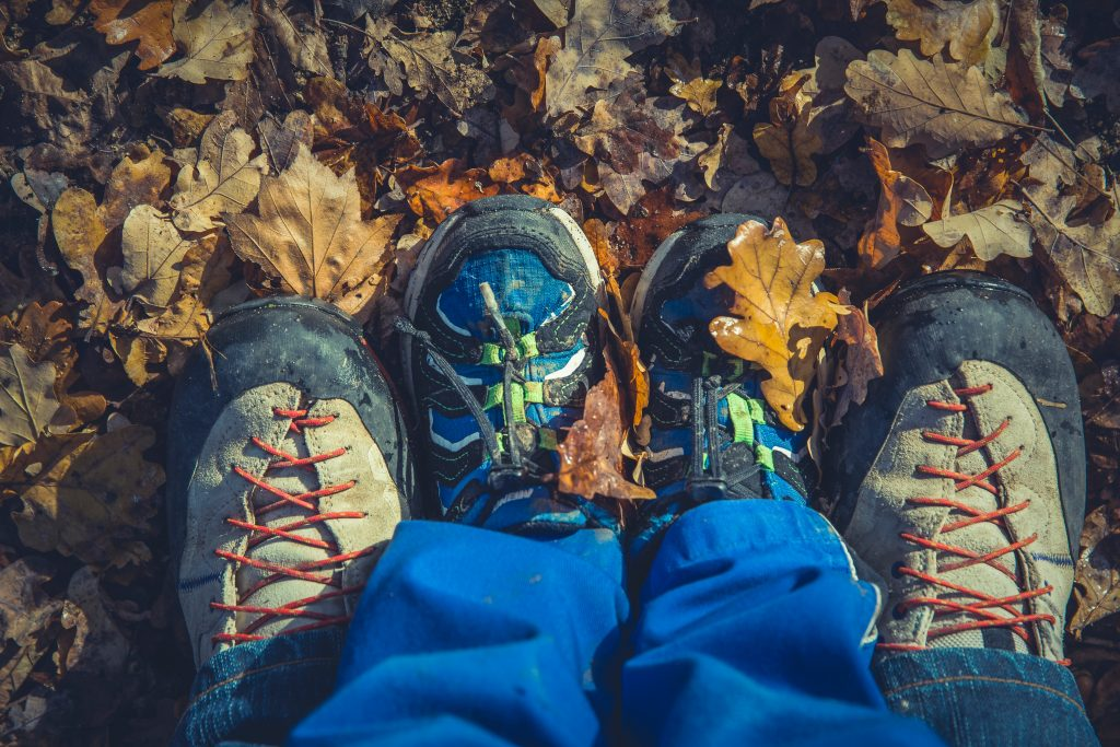 adult and kid feet standing together in autumn leaves