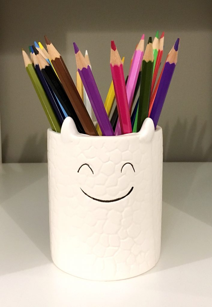ceramic jar with a monster smiley face filled with pencil crayons