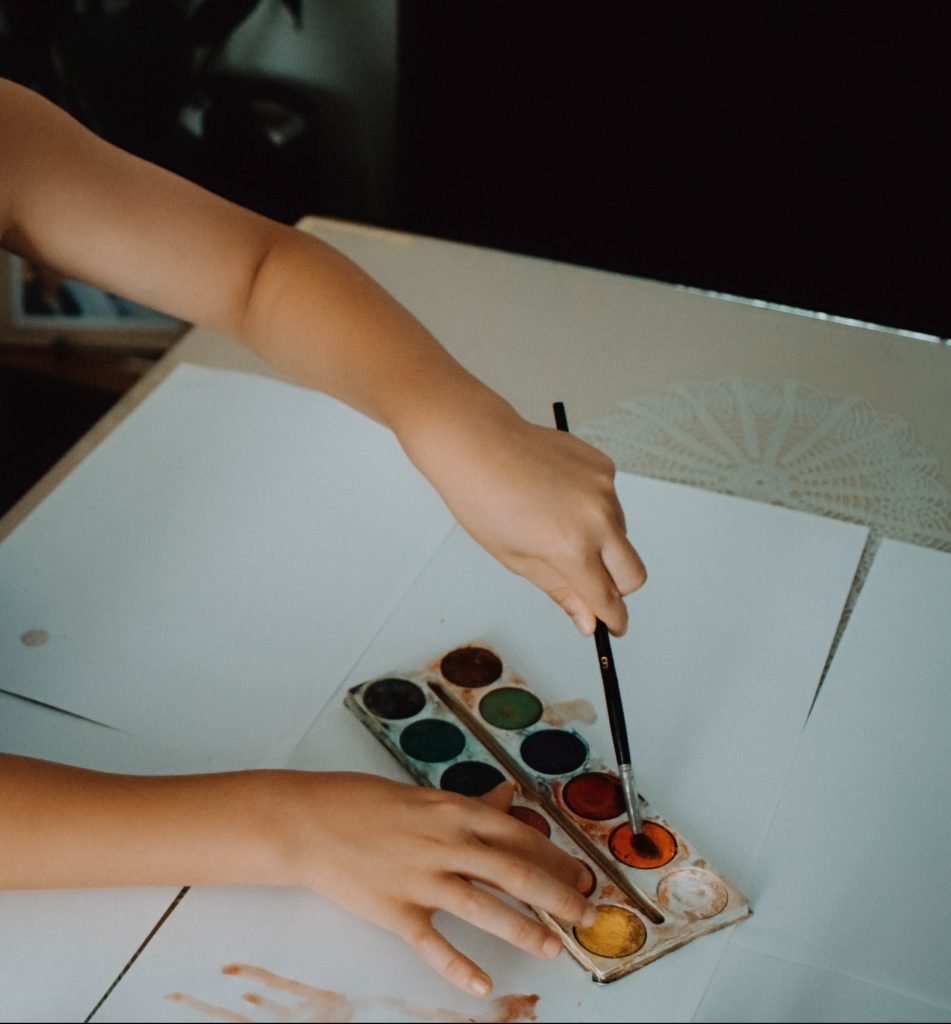small child sitting at a table using watercolour paints