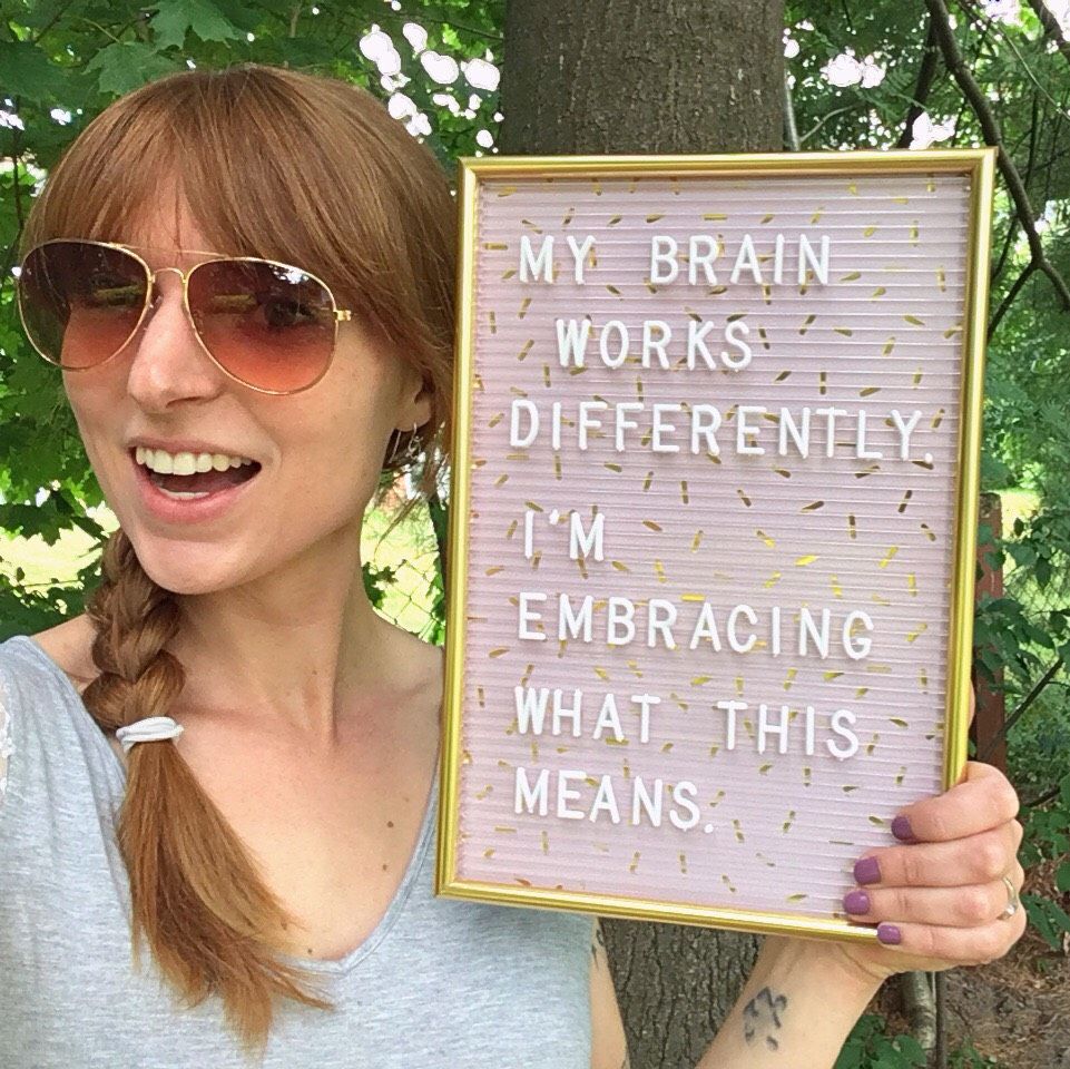 """Woman holding letter board that says """"My brain works differently. I'm embracing what that means."""""""
