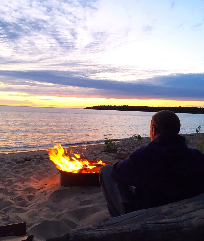 person sitting by a camp fire on the beach
