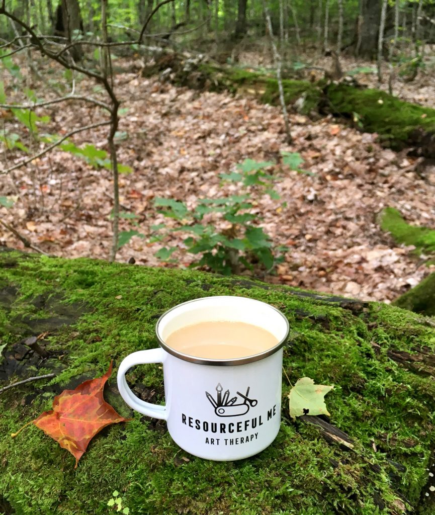 "photo of tin ""resourceful me art therapy"" camping mug on a mossy log in the forest"