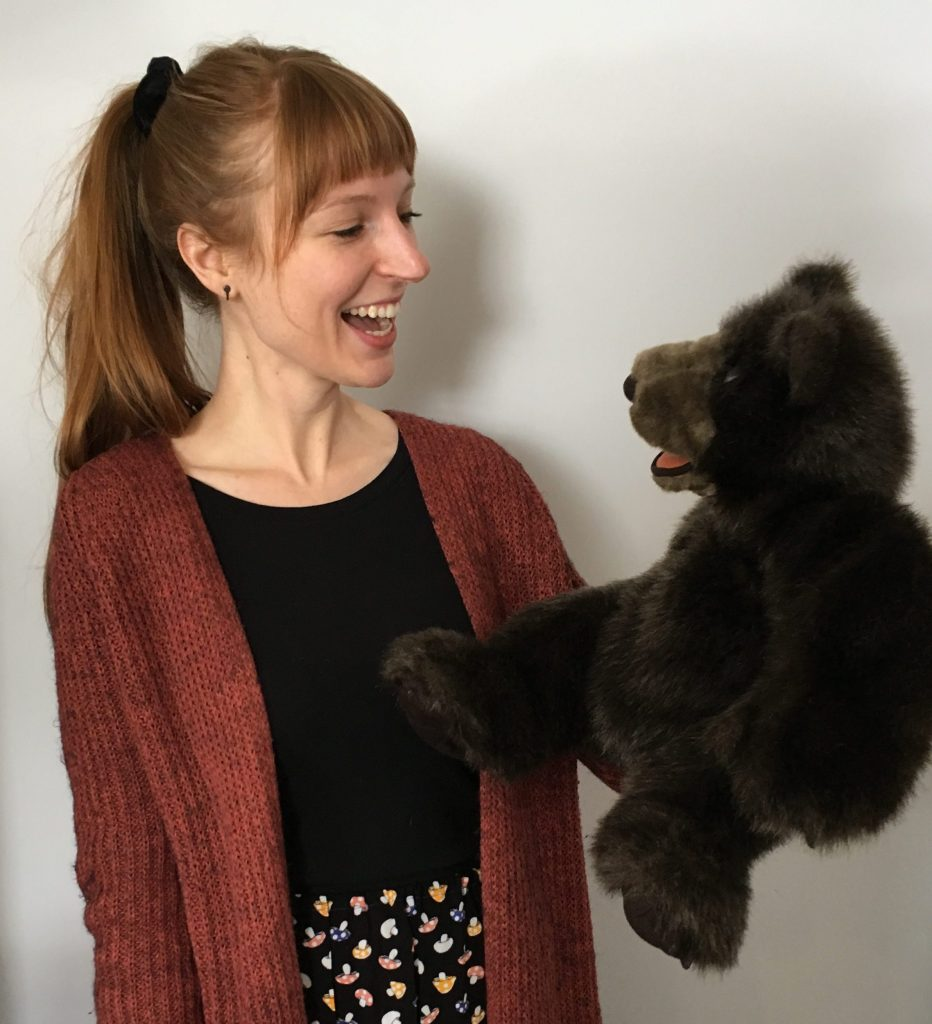 woman holding bear puppet and looking at it