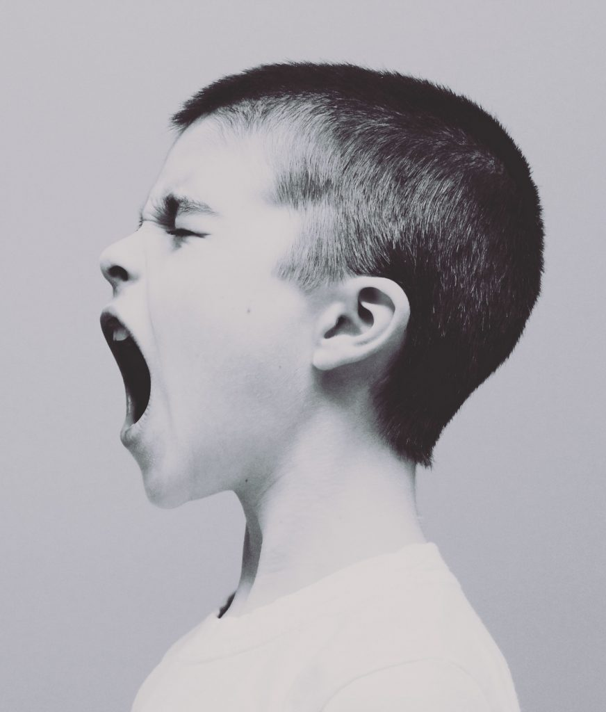black and white photo of boy yelling