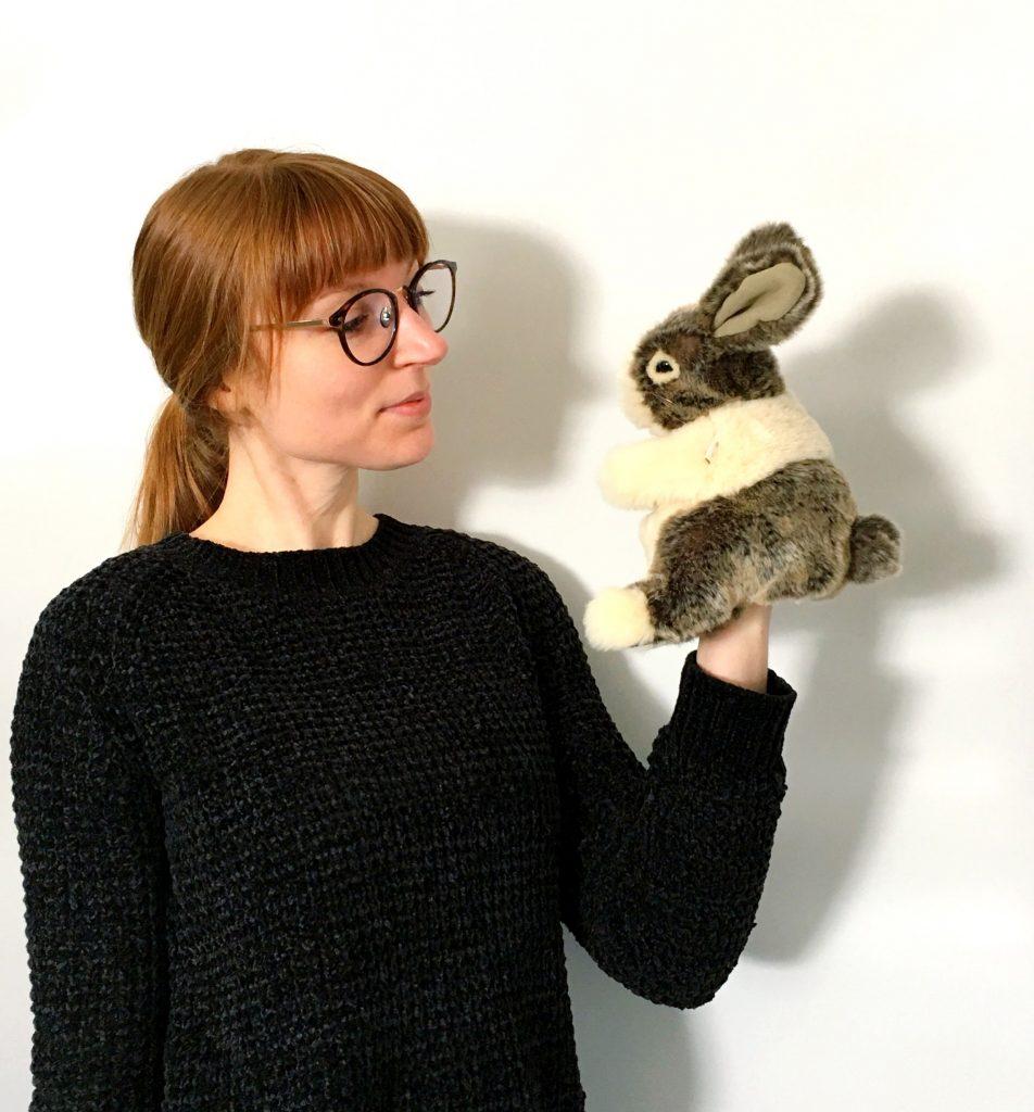photo of woman holding stuffed bunny puppet