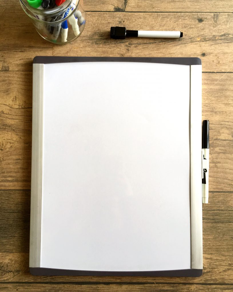 small whiteboard on table with dry erase markers