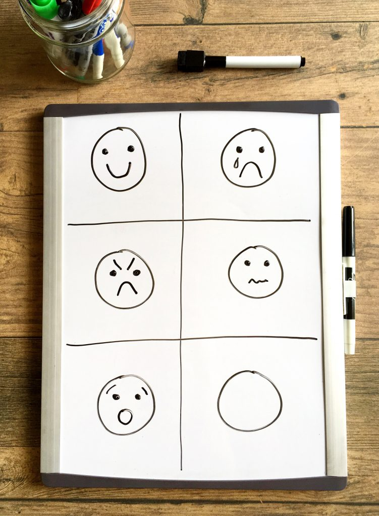 Small whiteboard with happy, sad, mad, worried, and surprised faces drawn on it