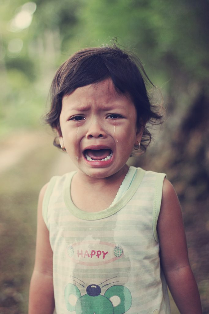 """child crying wearing shirt that says """"happy"""""""