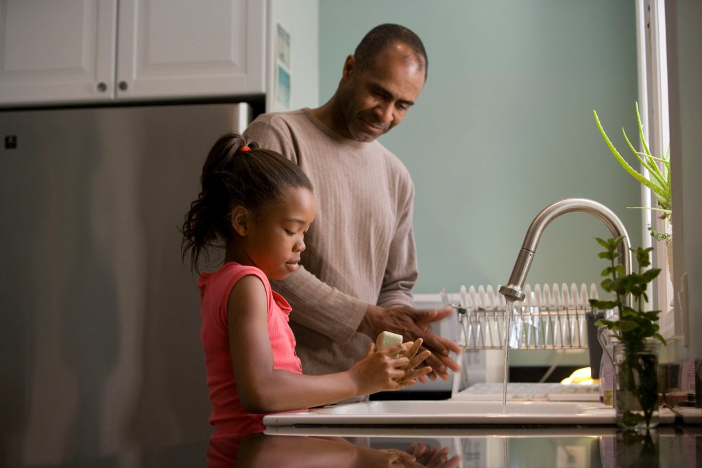 man and child washing hands at kitchen sink