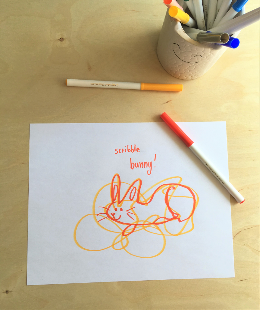 drawing of a bunny on top of a scribble, and two markers