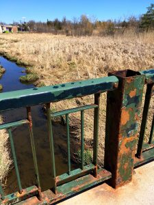 green rusted bridge over stream