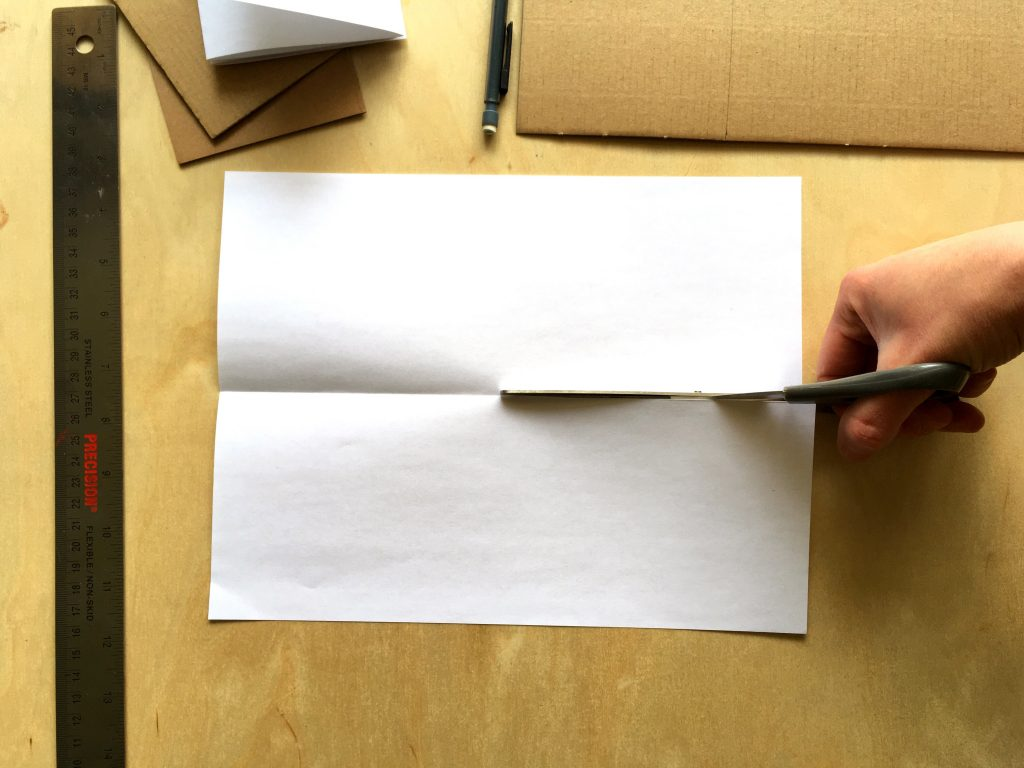 printer paper folded horizontally and being cut down the middle