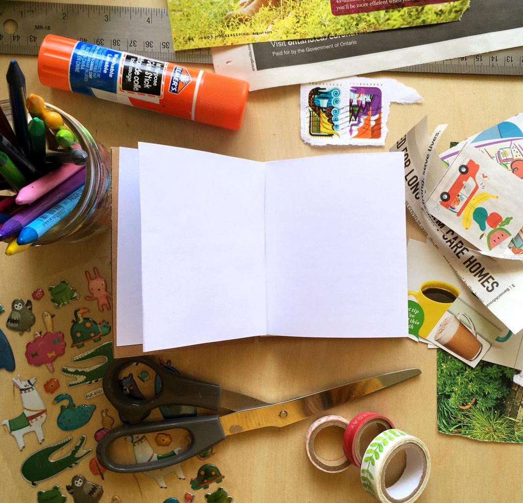 blank paper book surrounded by art supplies