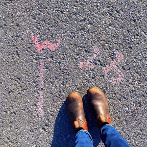photo of shoes beside municipal spraypaint road markings