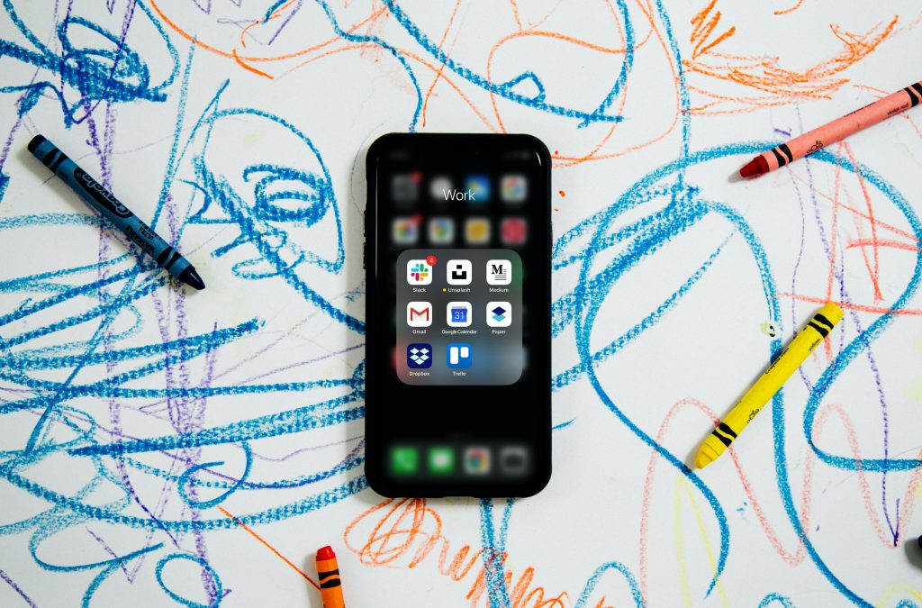 cell phone on top of child's crayon drawing