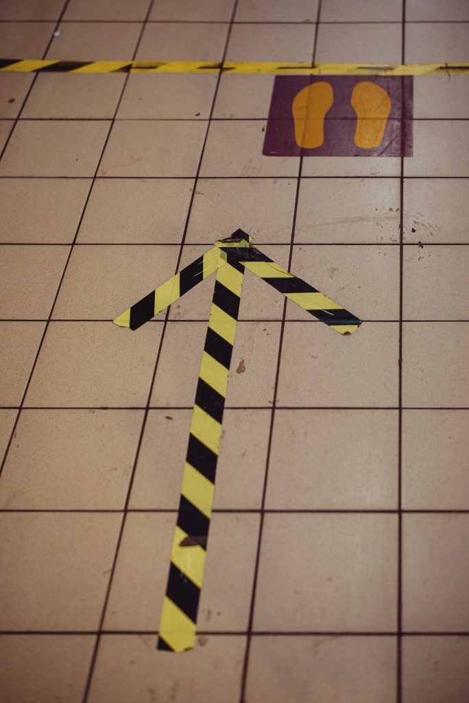 "arrow and ""stand here"" markings on floor for physical distancing"