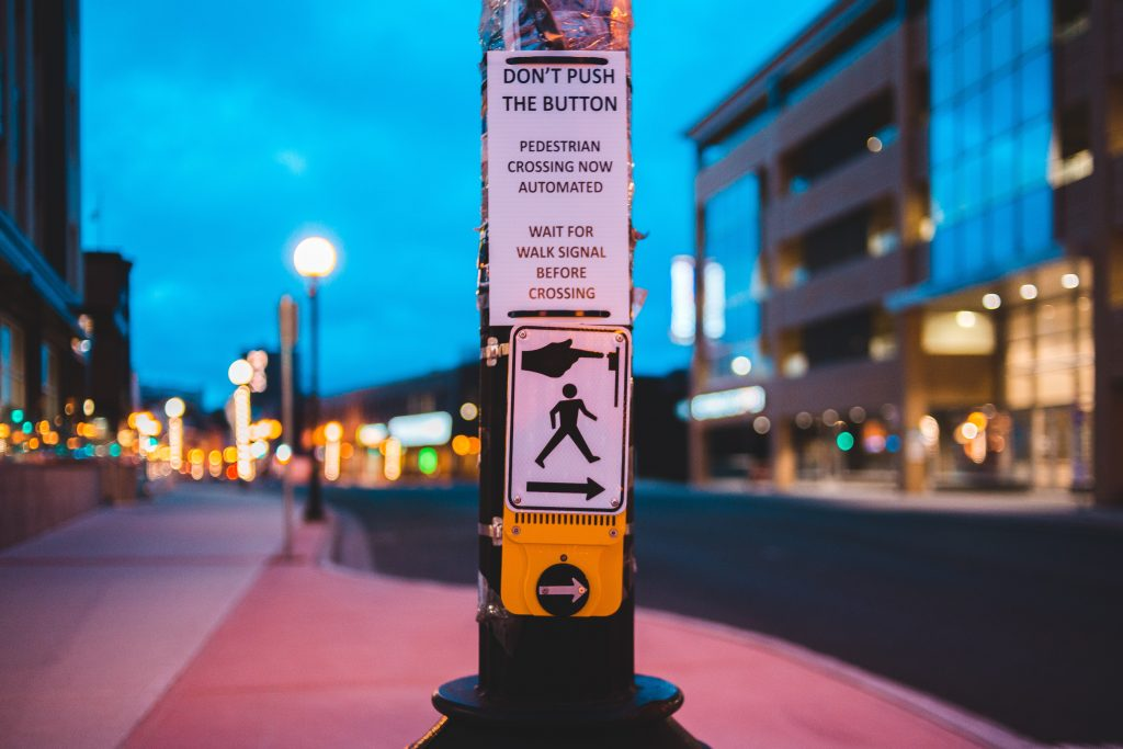 sign on crosswalk instructing pedestrians not to touch button