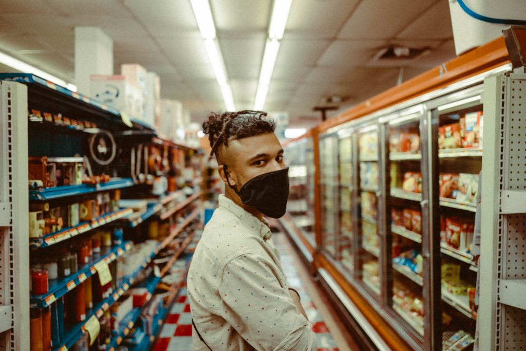 Black man wearing face mask in aisle of grocery store