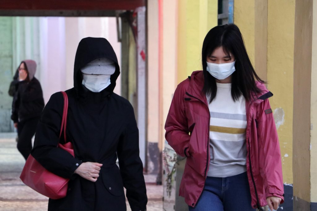 People walking down street wearing face masks