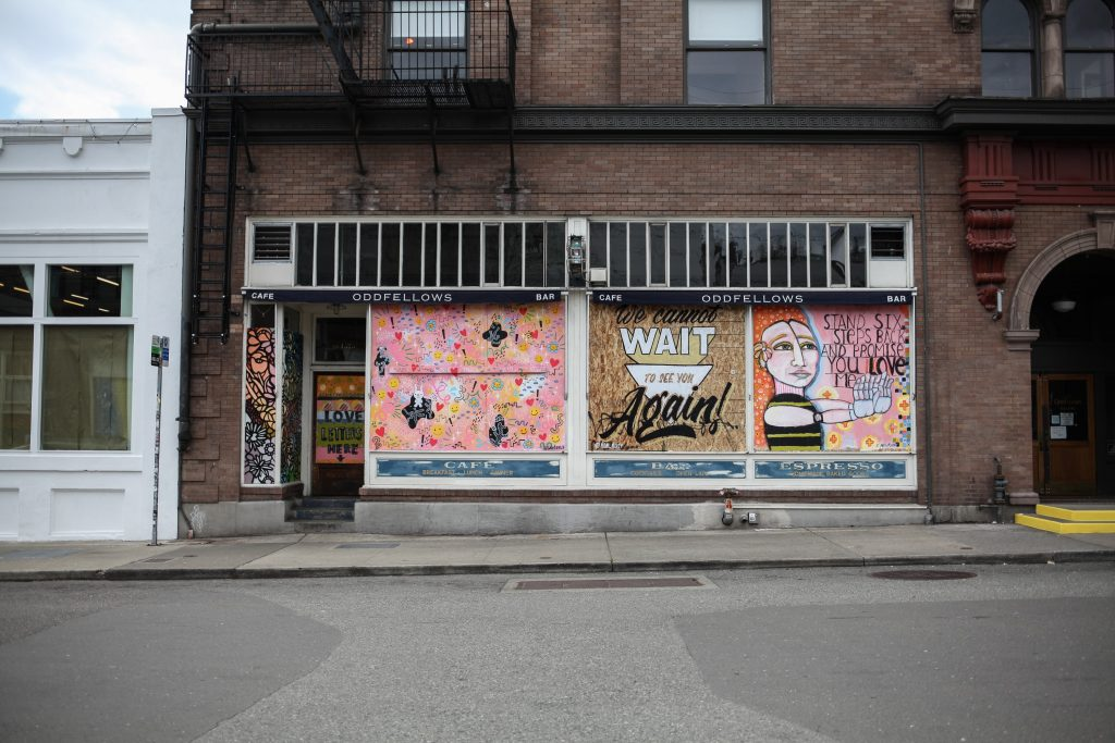 closed store front with murals over door and windows