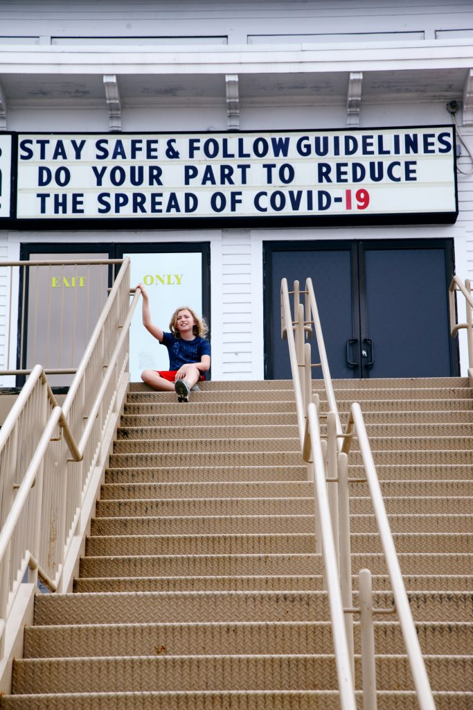 "Person sitting at top of stairs below a sign that says ""Stay Safe & Follwo Guidelines Do Your Part To Reduce the Spread of COVID-19"""