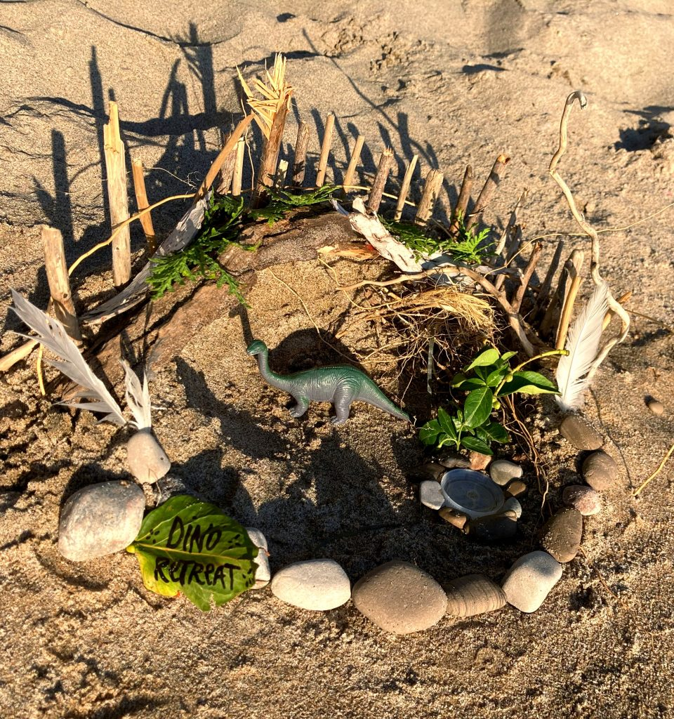 A sand, rock and stick house made on the beach with a plastic dinosaur inside.