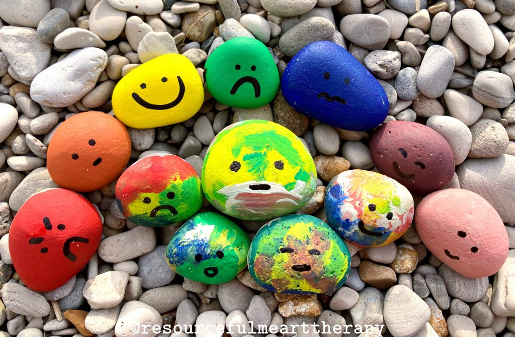 Rocks on the beach painted in rainbow colours with feeling faces drawn onto them