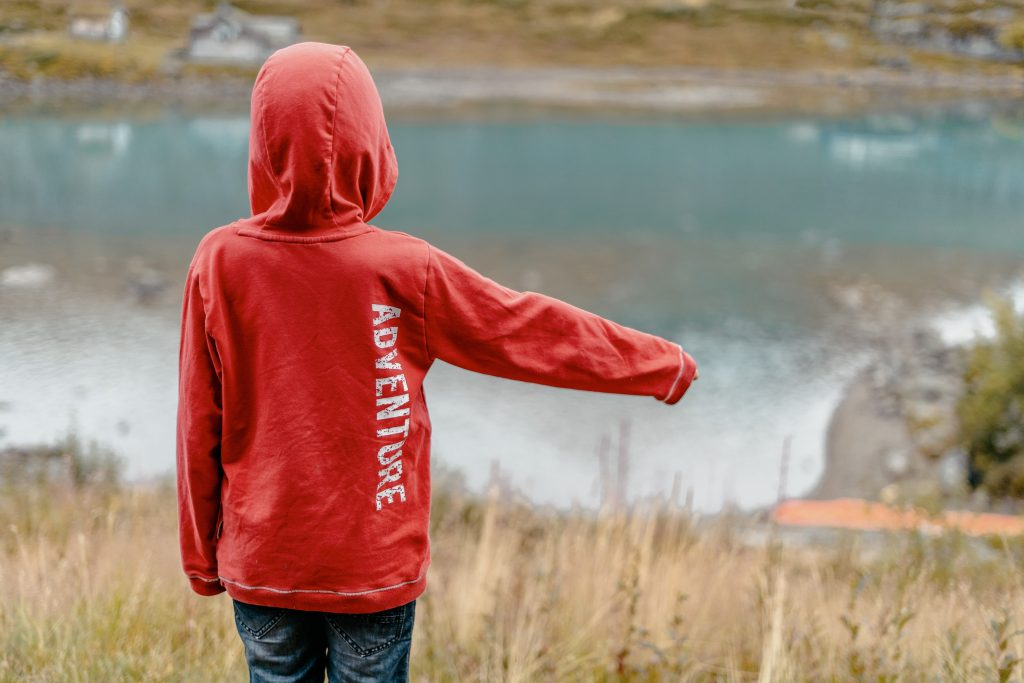 "child wearing a sweatshirt that says ""adventure"" pointing down a hill"