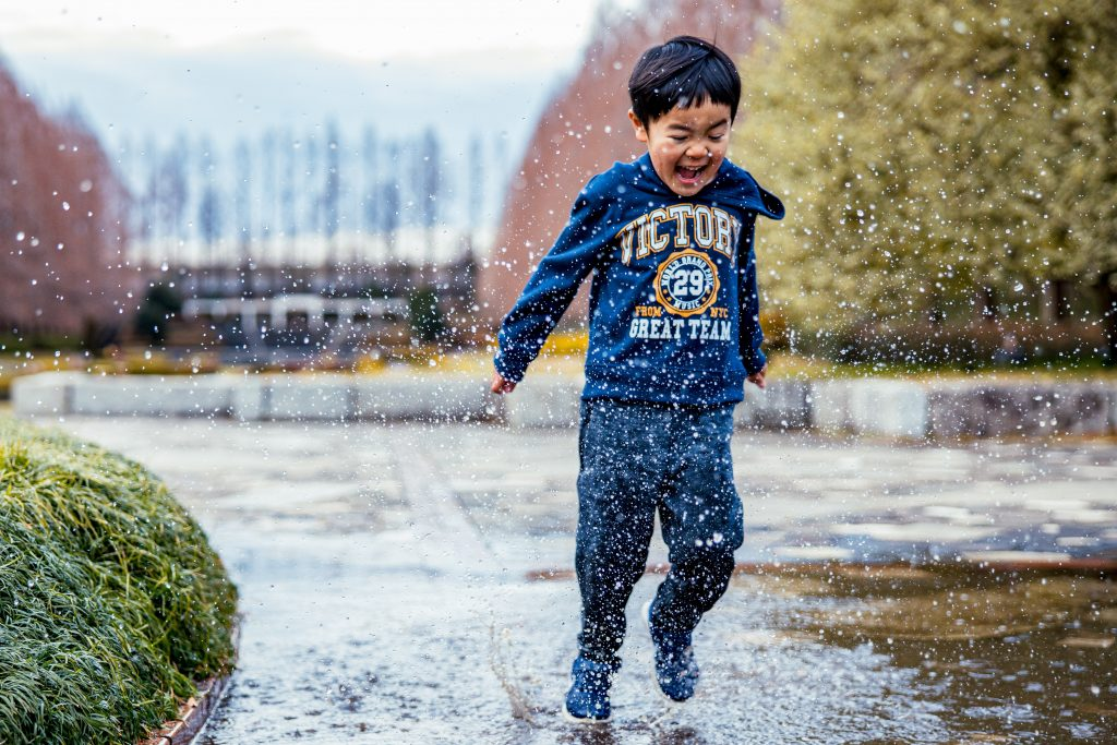 Boy with dark hair smiling and running through a puddle