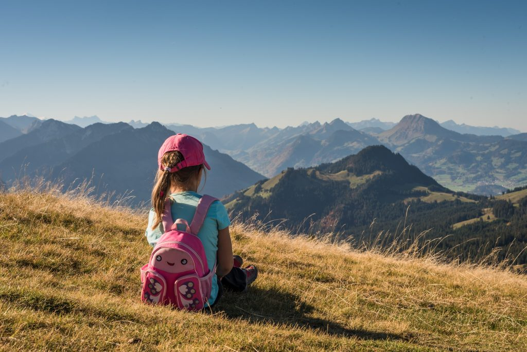 child sitting in mountains wearing backpack and baseball hat