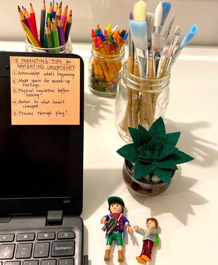 post-it note with a list of parenting tips on a laptop screen, with art supplies and toys beside the laptop on the desk