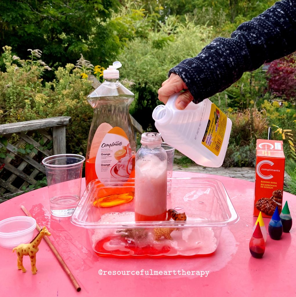 hand pouring vinegar into a plastic bottle containing dish soap, food colouring, water and baking soda