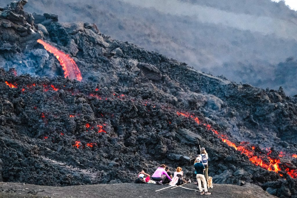 Family standing on rock watching lava cascade down a ridge