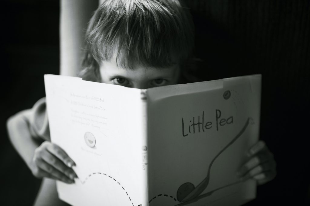 child looking angrily over a book