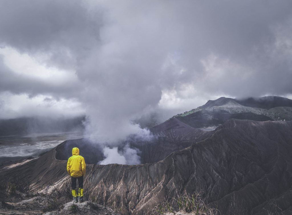 Person in rain gear watching smoke billow from a volcano in the distance