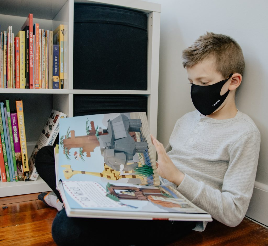 photo of child wearing a mask and reading a picture book