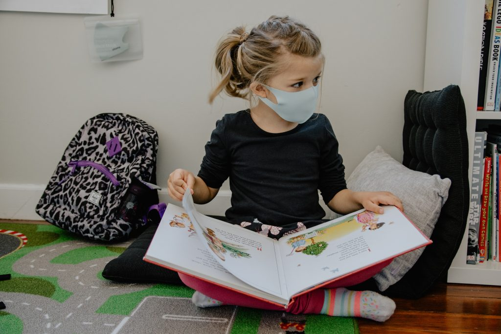 Photo of child wearing a face mask and sitting on the floor looking at a picture book