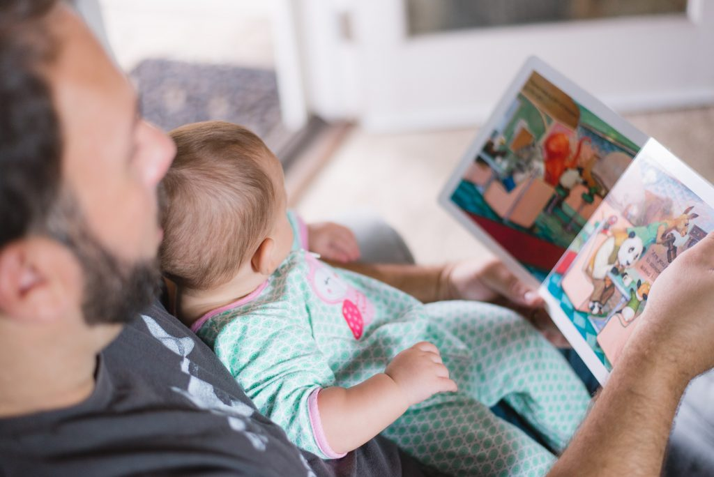 man holding baby and reading picture book
