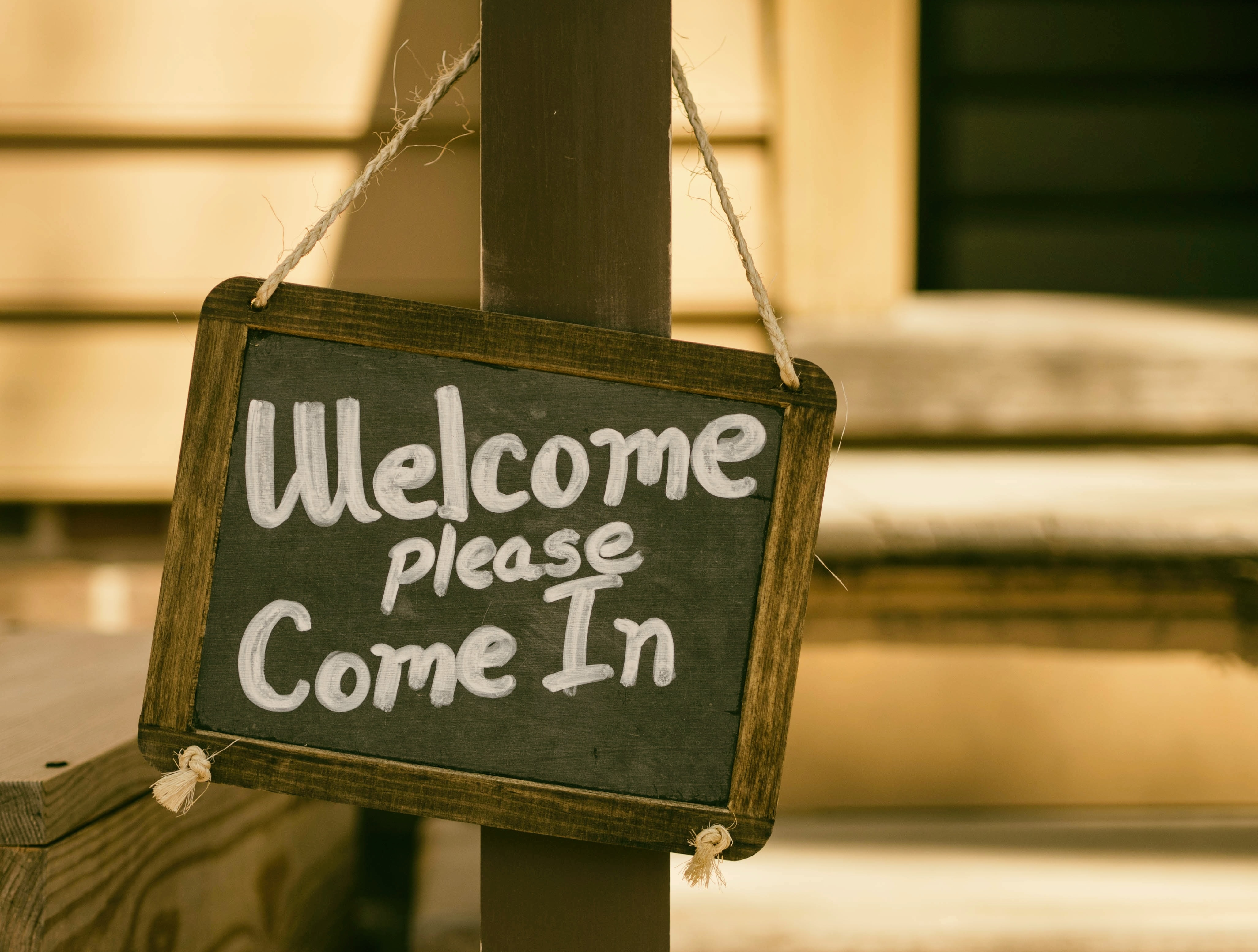 """small chalkboard sign that says """"welcome, please come in"""""""