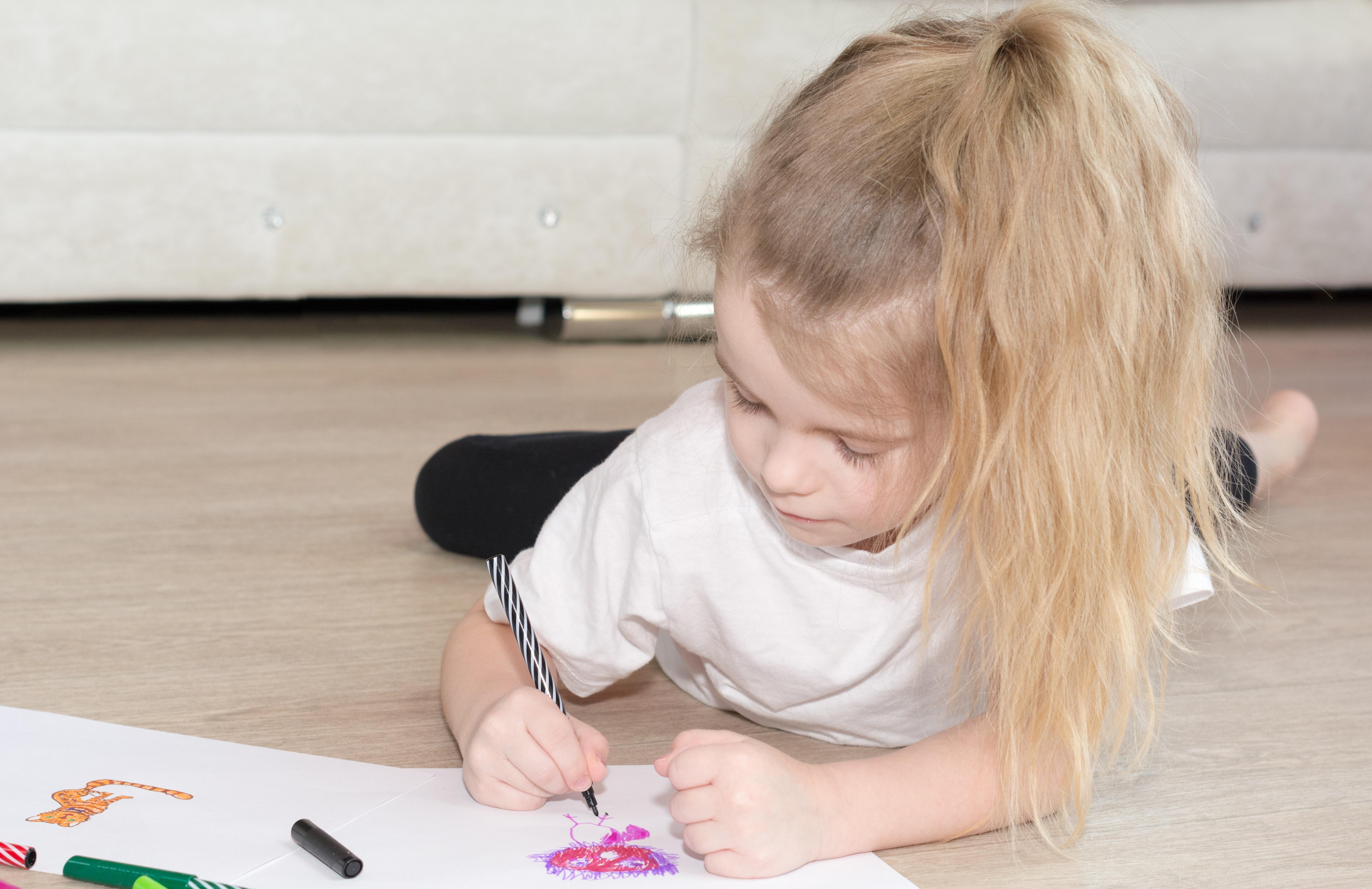 photo of girl lying on the floor drawing
