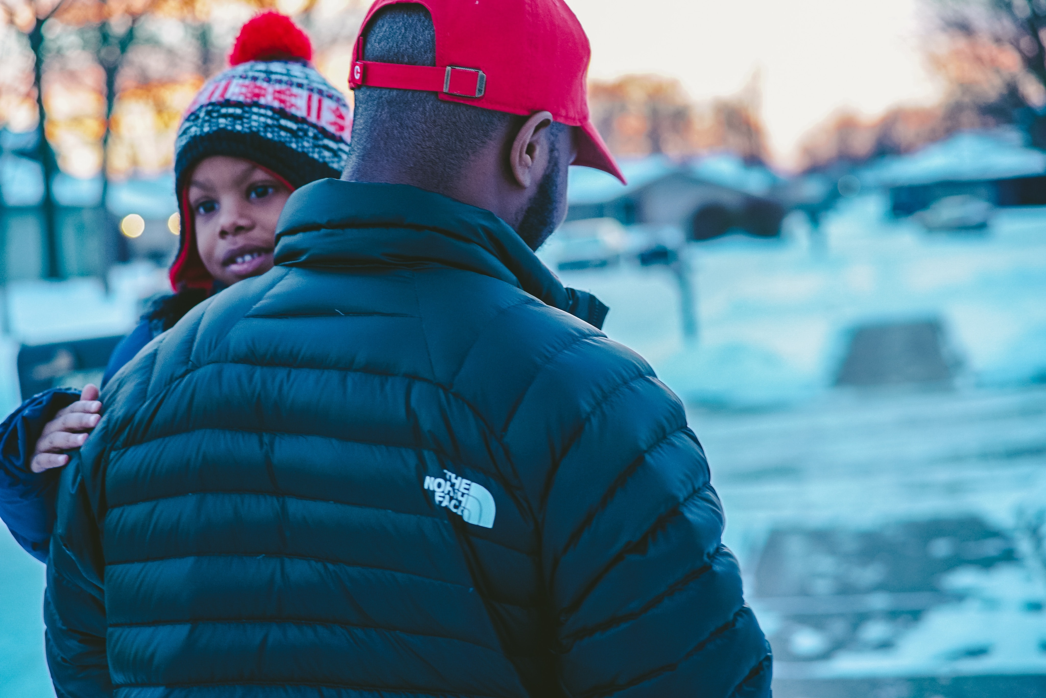 Man carrying child outside wearing winter clothes