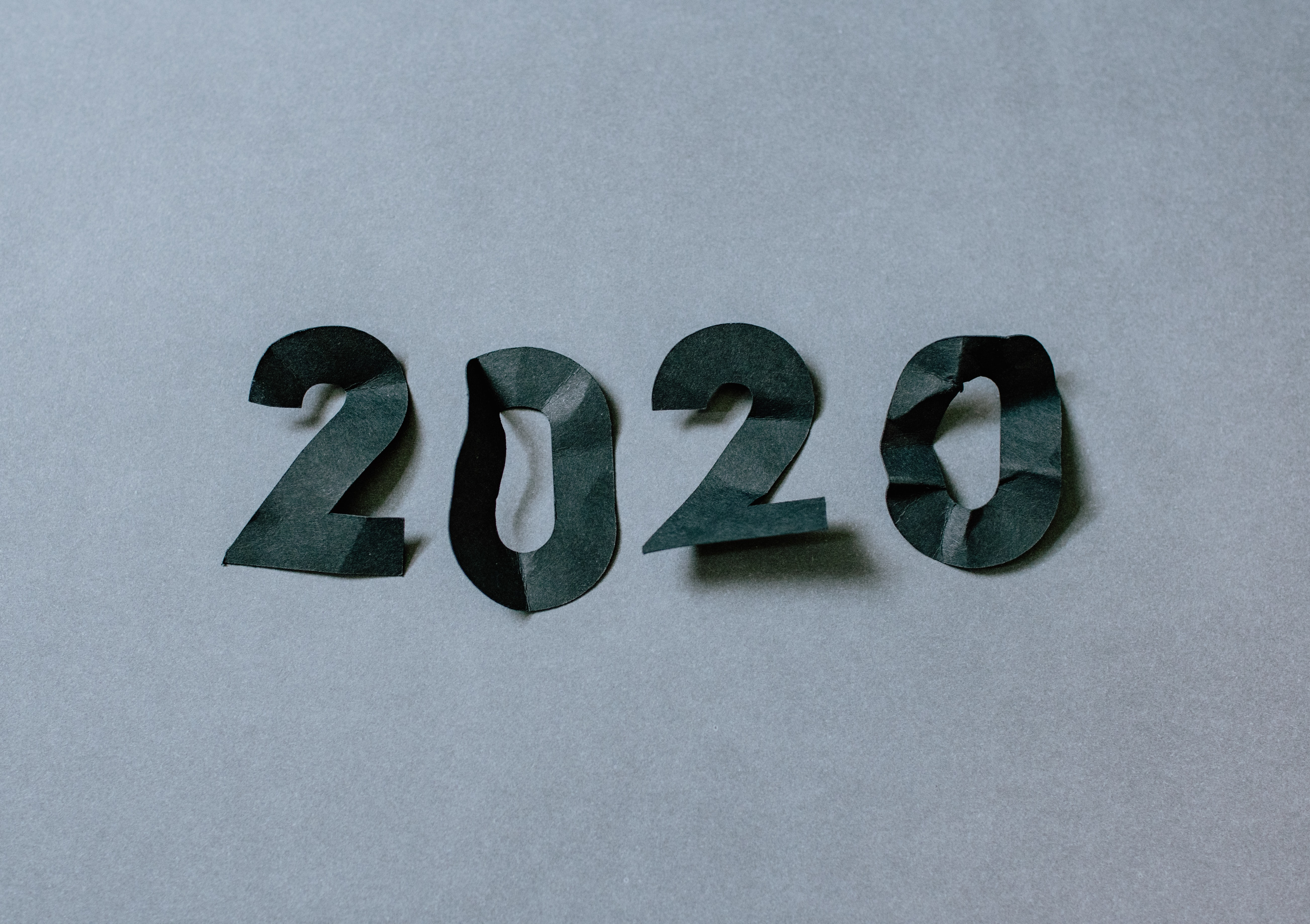 """black construction paper numbers """"2020"""" crumpled against a white background"""