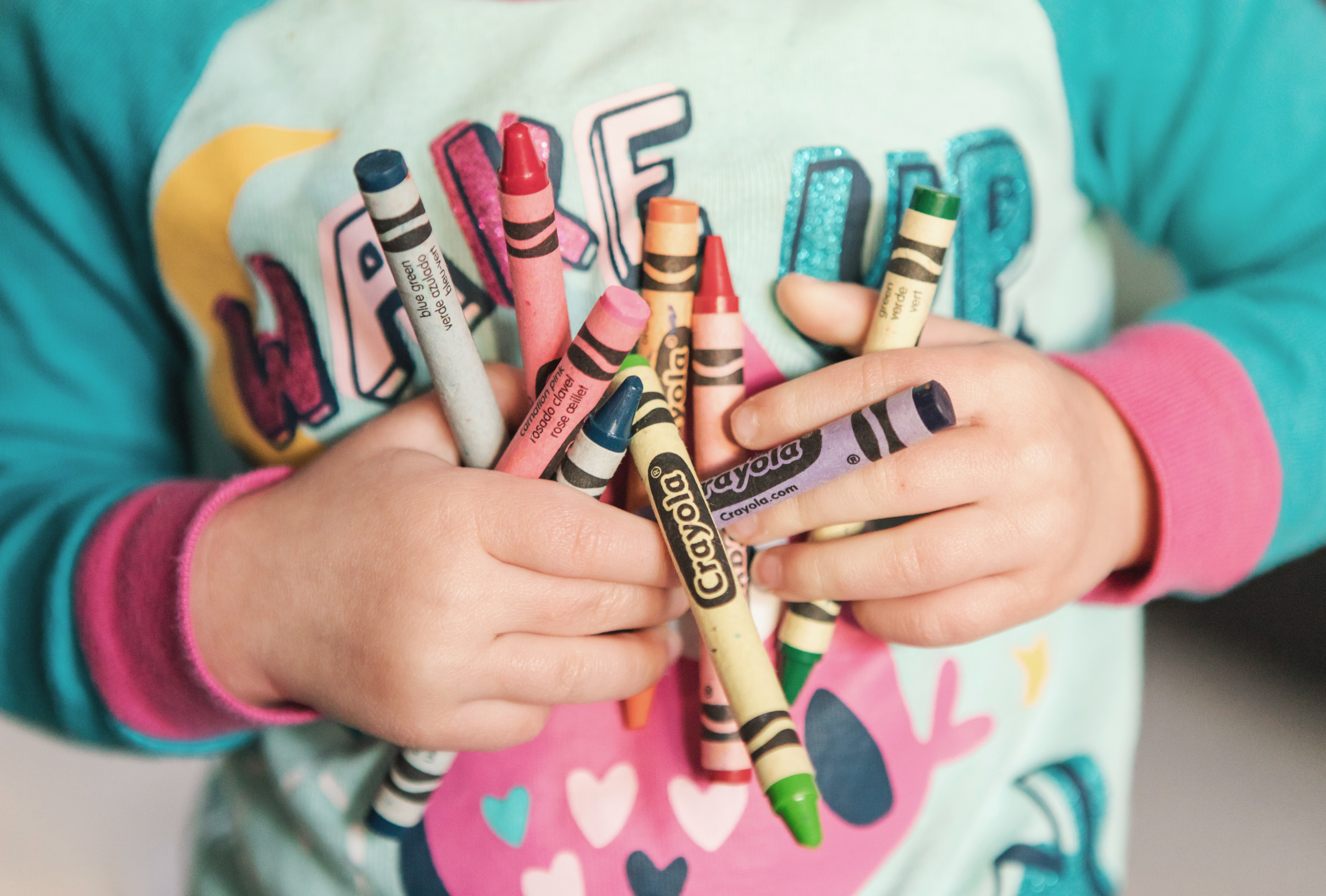 close up of small child's hands holding crayons